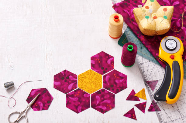 preparation of hexagon pieces of fabric for sewing a quilt grandmother's flower garden - quilt stock photos and pictures
