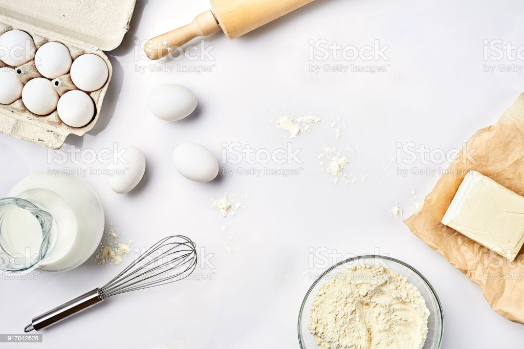Preparation of the dough. A measurement of the amount of ingredients in the recipe. Ingredients for the dough: flour, eggs, rolling pin, whisk, milk, butter, cream. Top view, space for text royalty-free stock photo