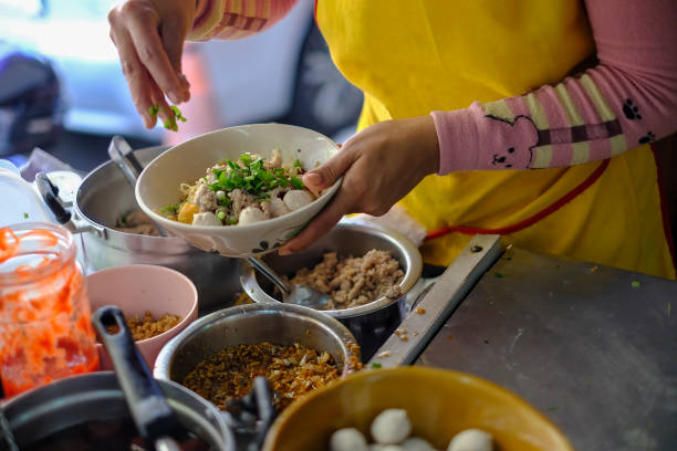Preparation of the tasty world famous Thai noodle soup in Bangkok. stock photo