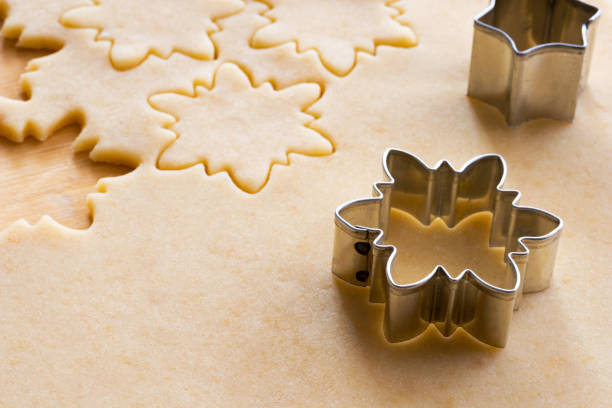 Preparation of traditional Linzer Christmas cookies - cutting out star shapes Preparation of traditional Linzer Christmas cookies - cutting out star shapes from rolled out dough cookie cutter stock pictures, royalty-free photos & images