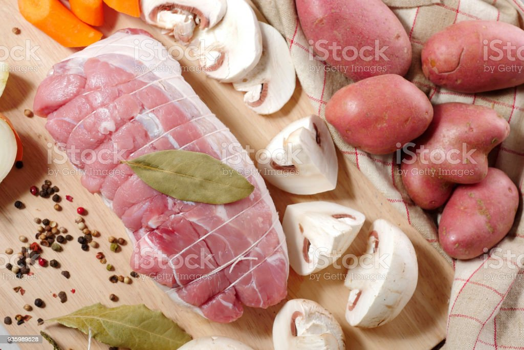 preparation of uncooked roast pork with the mushrooms and potatoes stock photo
