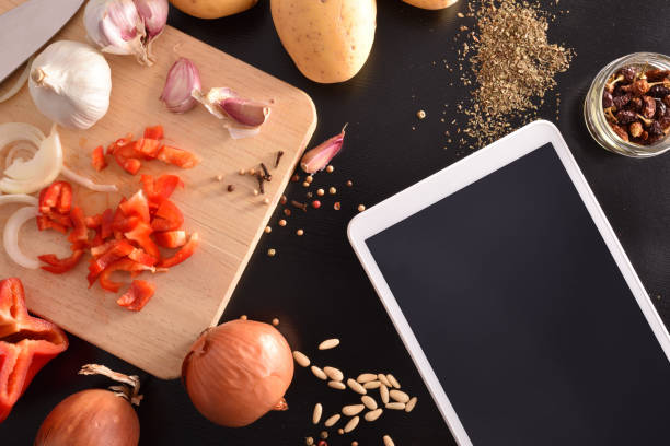Preparación de verduras en la mesa de madera negra con la parte superior de la tableta - foto de stock