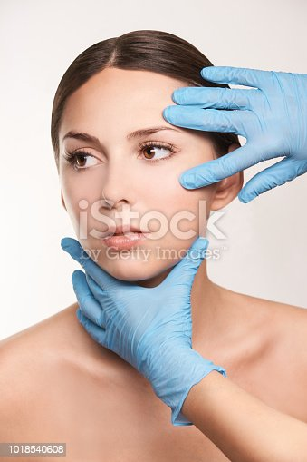 istock Preparation operation. Doctor hands. Medical procedure. Beautiful girl 1018540608