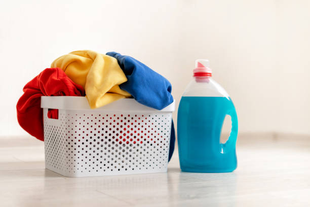 Preparation to laundry process. Close up photo of gel soap bottle standing on laminate floor inside flat with bright interior near basket with colorful clothes Preparation to laundry process. Close up photo of gel soap bottle standing on laminate floor inside flat with bright interior near basket with colorful clothes laundry detergent stock pictures, royalty-free photos & images