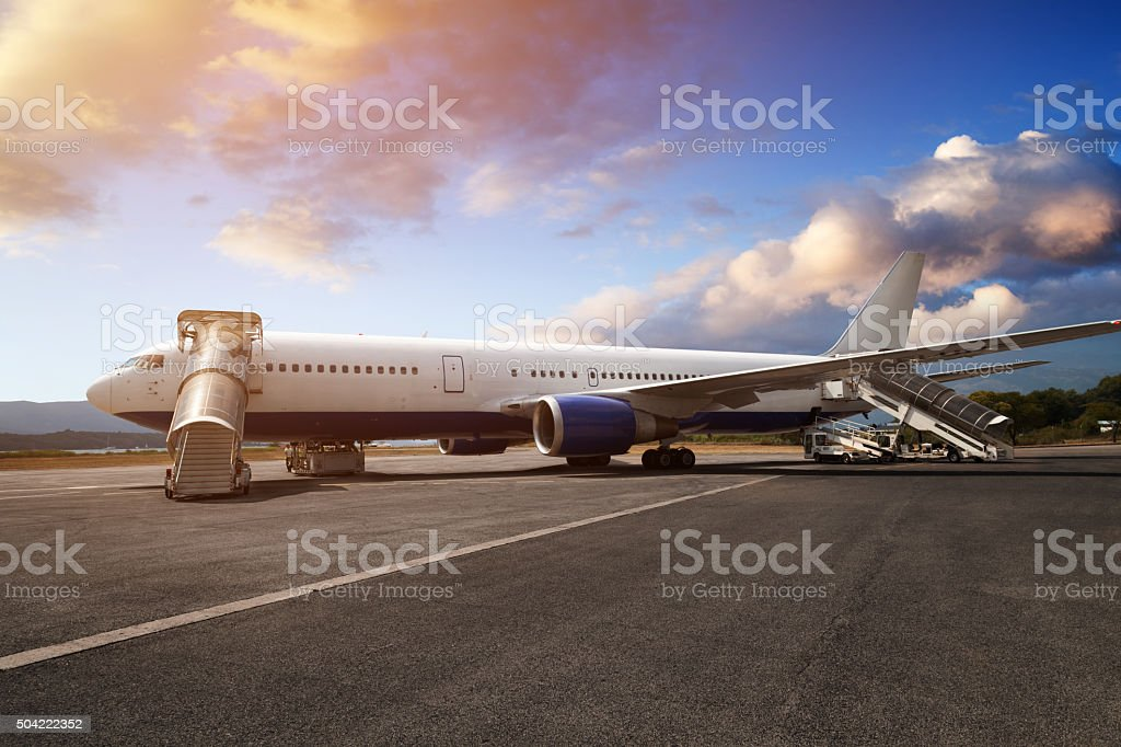 Preparations of passenger jet airplane in airport in the evening stock photo