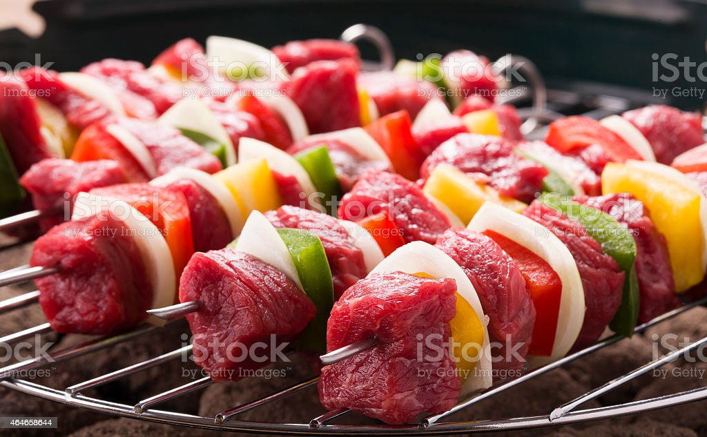 Prepared beef skewers on a grill ready for a barbecue stock photo