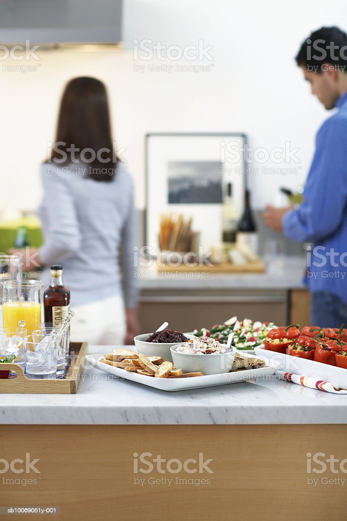 Prepared food on kitchen counter, Man and woman in background. Lizenzfreies stock-foto