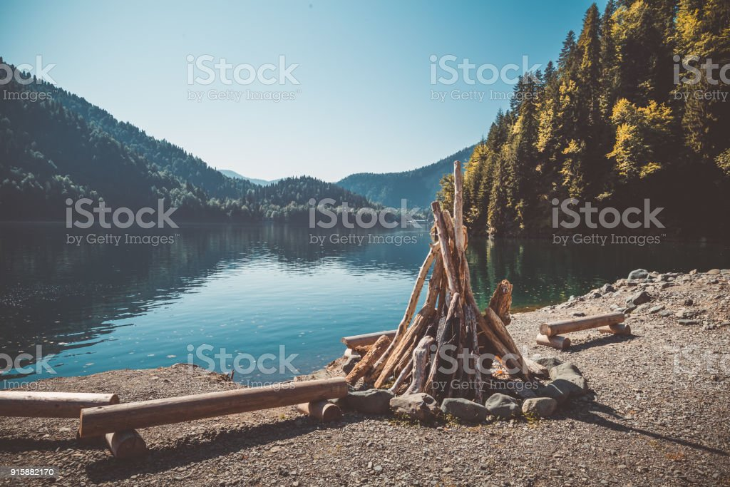 Prepared for kindling a large bonfire and benches from the logs on the shore of a beautiful lake with clear water surrounded by mountains and forest. Toned image stock photo