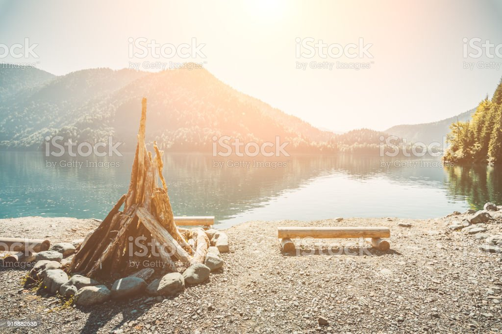 Prepared for kindling a large bonfire and benches from the logs on the shore of a beautiful lake with clear water surrounded by mountains and forest on the background of bright summer sun stock photo