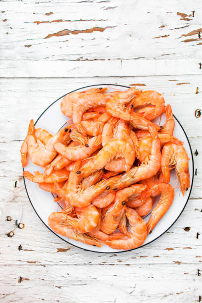 Prepared shrimps on a white plate over old white wooden table with picture id929636710?b=1&k=6&m=929636710&s=612x612&w=0&h=5br3fbo 3zzn7uuuztvfickrjlxoylnak  v 7l pec=