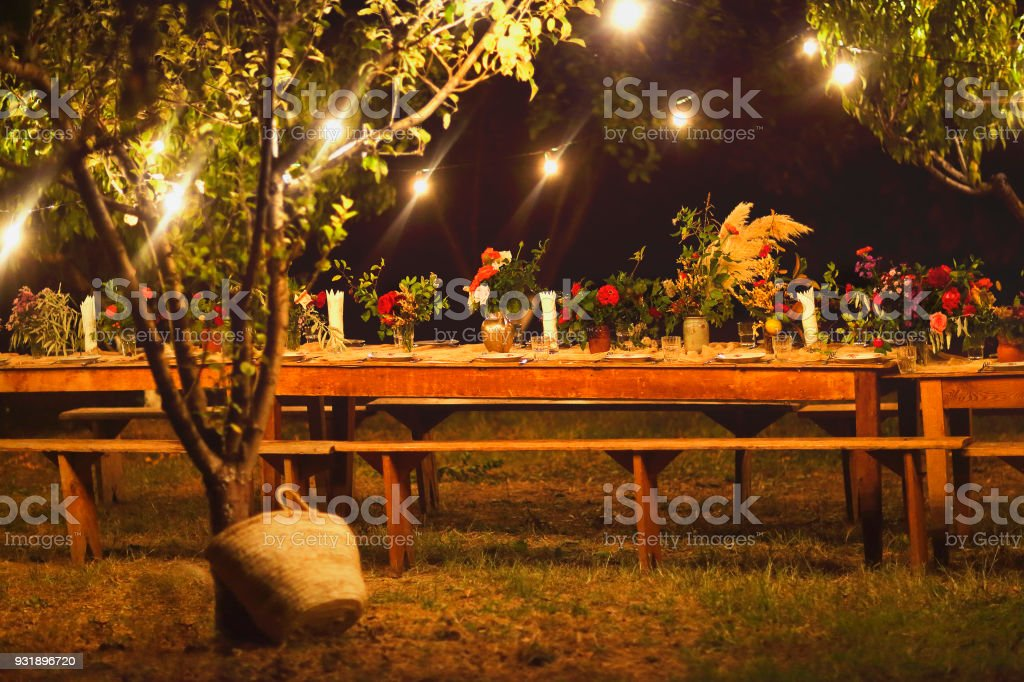 Prepared table for a rustic outdoor dinner at night with wineglasses, flowers and lamps stock photo