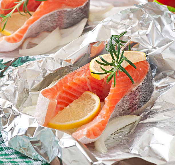 raw salmon steaks on foil with lemon and rosemary