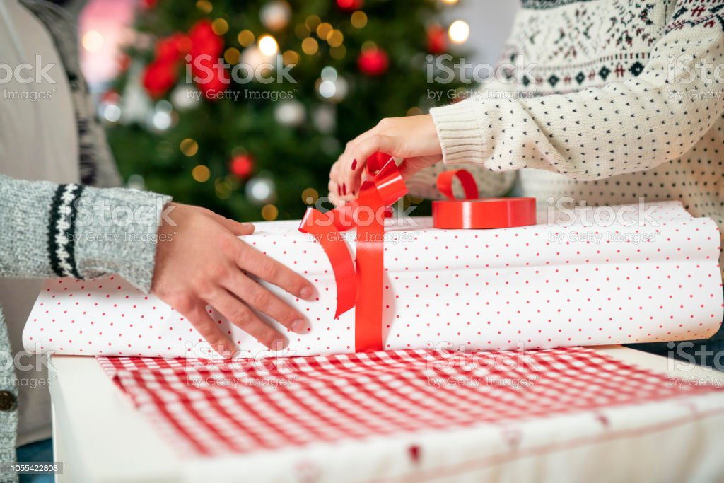 Unrecognizable, young man and woman packing a Christmas gift together.