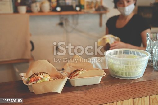 Preparing a delicious Fresh BLT Sandwich with Bacon Lettuce and Tomato at Cafe.  After Pandemic,  Two woman wearing mask and face shield.
