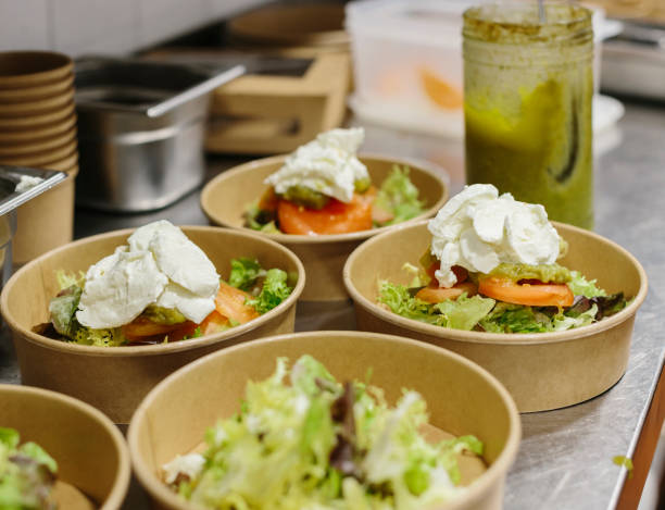 Preparing a endive and fresh cheese salad to take away. The containers used are compostable. stock photo