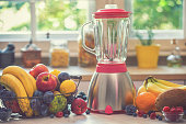 Blender and various fresh fruits in the kitchen for preparing healthy smoothies