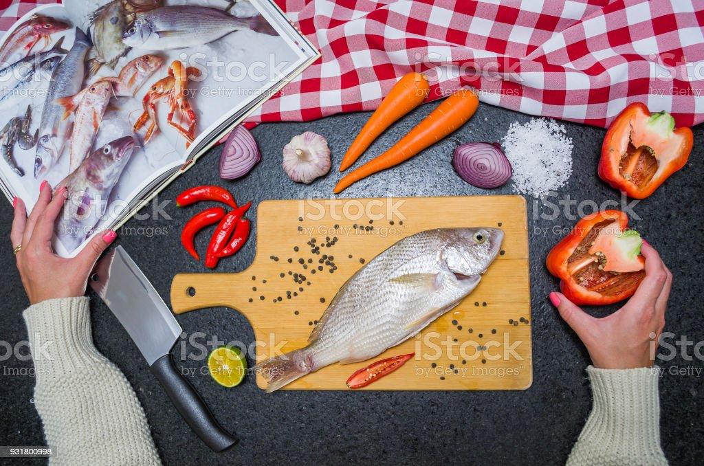 Preparing a gastronomic dish of roasted Croaker Fish stock photo