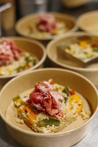 Preparing a ham salad with rice to take away. The containers used are compostable. stock photo