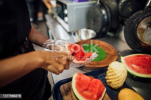 Vietnamese female in her kitchen at work preparing an exotic fresh fruit salad.