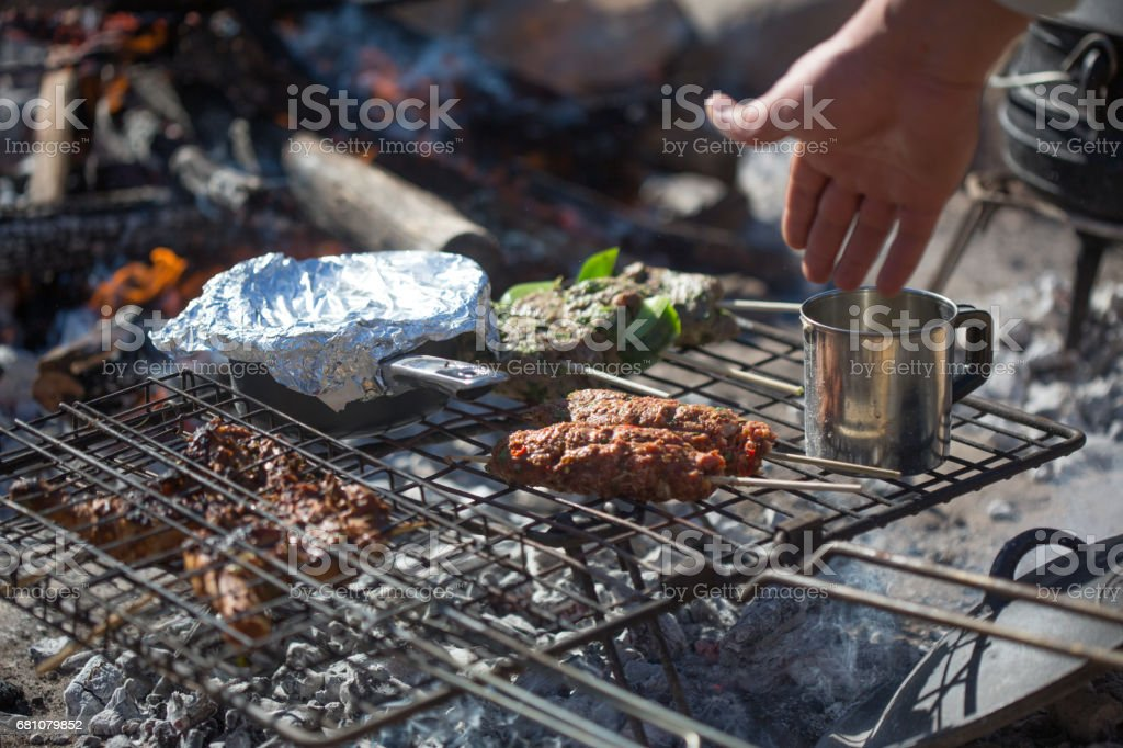 Preparing a meal over an open fire in the outdoorsl it bb royalty-free stock photo