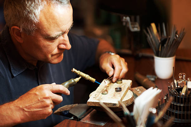 Preparing a new set of rings Jeweller using a blowtorch while he works on a ring jeweller stock pictures, royalty-free photos & images