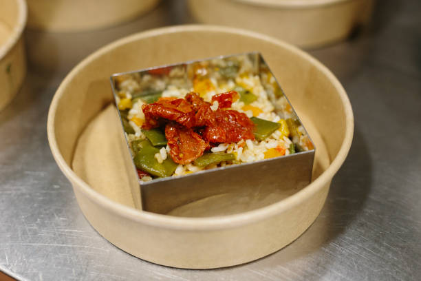 Preparing a rice salad in a mold to take away. The containers used are compostable. stock photo