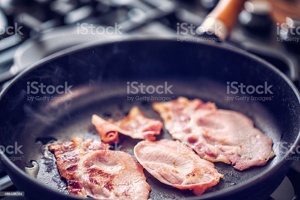 Preparing and Roasting Bacon in a Pan stock photo