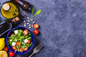 Top view of a blue bowl full of fresh salad surrounded by various ingredients like arugula leaves, cherry tomatoes, pine nuts, and some salad dressing ingredients like balsamic Vinegar, lime, olive oil and pepper. All the objects are at the left side of the image leaving a useful copy space at the right side on a rustic grey bluish backdrop. Studio shot taken with Canon EOS 6D Mark II and Canon EF 24-105 mm f/4L
