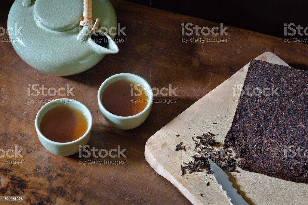 Preparing and Serving Chinese Compressed Brick Tea from Celadon Tea-ware stock photo