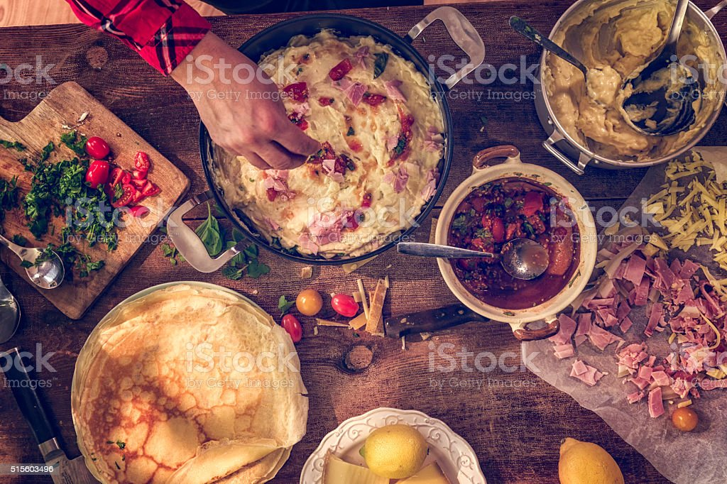 Preparing Baked Crepes Pancakes with Ham and Tomatoes stock photo