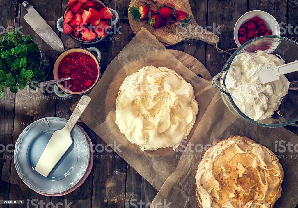 Preparing Berry Pavlova Cake with Strawberries and Raspberries stock photo