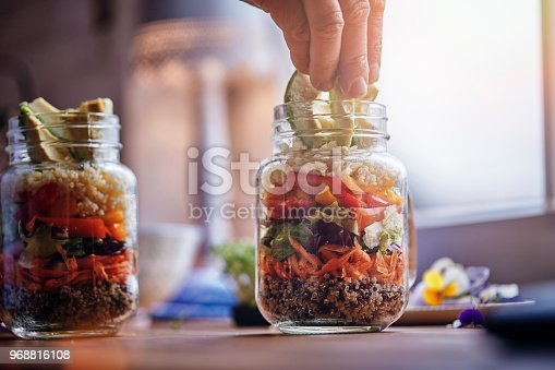 Preparing Bulgur Salad with Paprika, Cucumber, Onion, Carrots, Lettuce and Quinoa served in a Jar