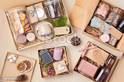 Preparing care package, seasonal gift box with coffee, cookies, candles, spices and cups. Personalized eco friendly basket for family and friends for thankgiving, christmas, mothers and fathers day holidays.