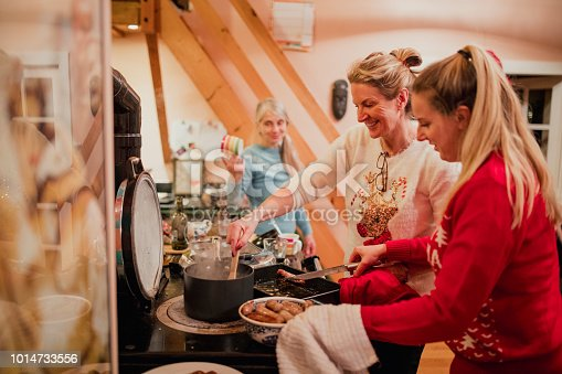 Three women are preparing christmas breakfast in the kitchen at home. They are cooking sausages and onions.