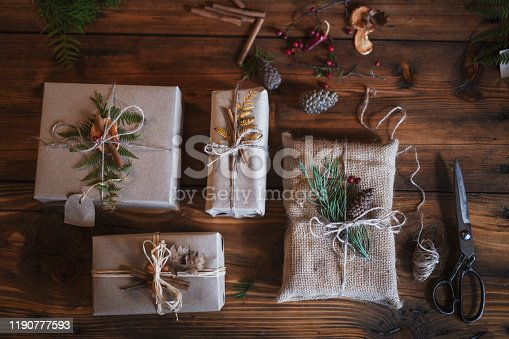 Unrecognizable male hands wrapping Christmas presents with natural materials, plastic free, organic wrapping with paper.