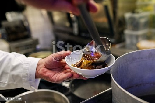 Chef carefully pouring a ladle full of  consommé into a bowl that contains a delicate mix of peas and carrots and  a smoked egg yolk. Colour, horizontal with some copy space. Shot on location in a restaurant on the island of Møn in Denmark.