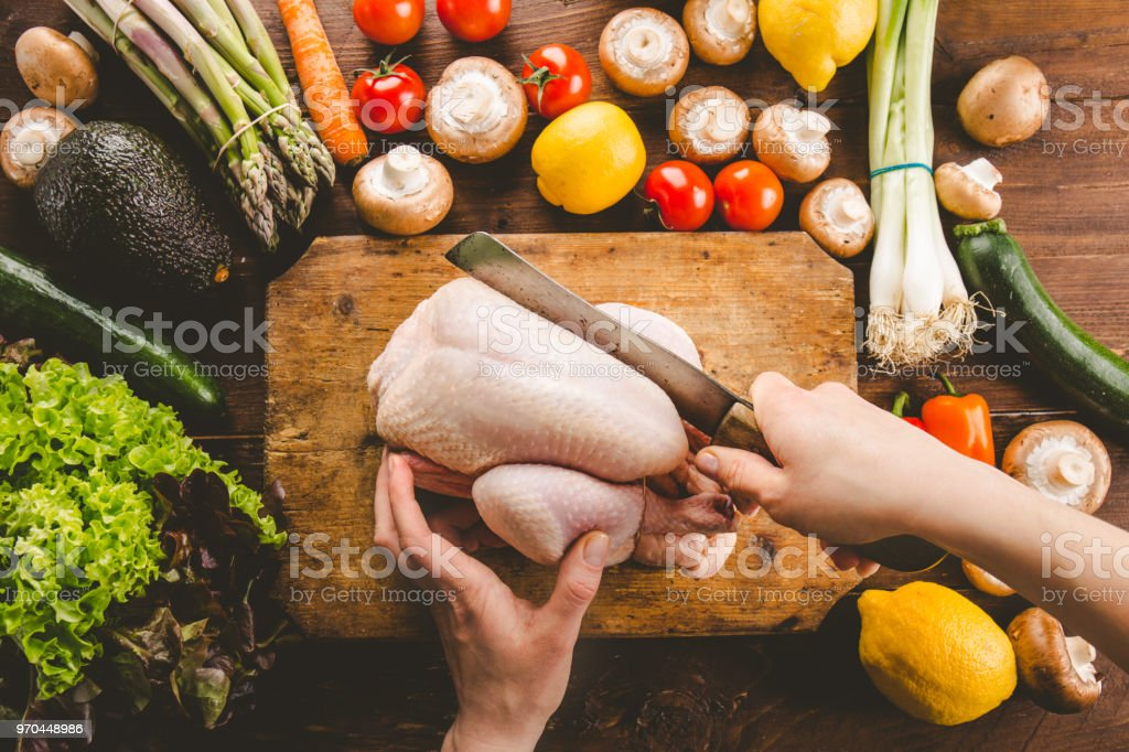 Top View of Preparing Cutting fresh raw chicken. Hands of young cook...