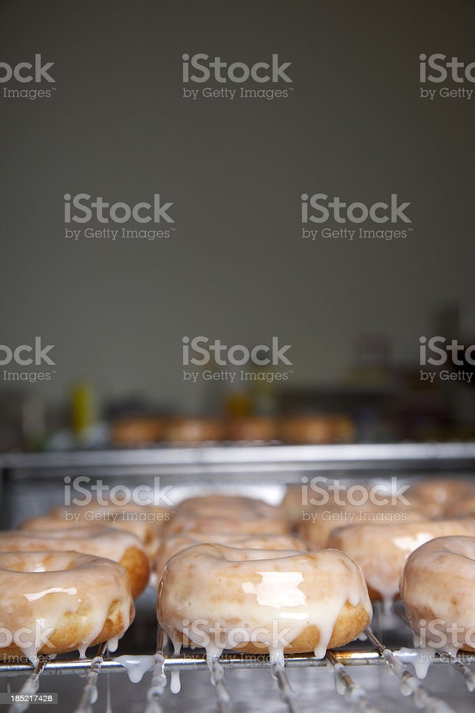 Preparing donuts in a bakery putting on the glaze stock photo