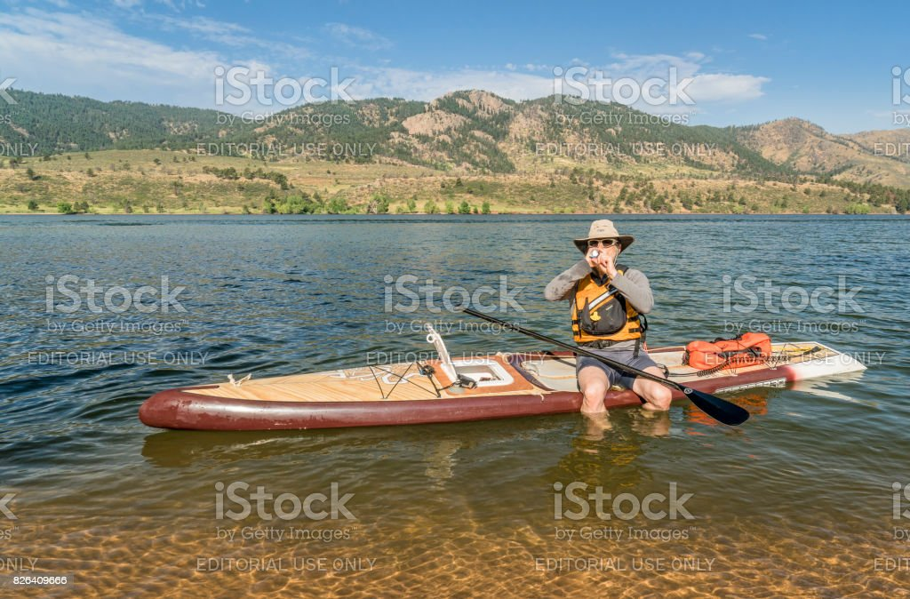 Preparing expedition stand up paddleboard for a trip stock photo