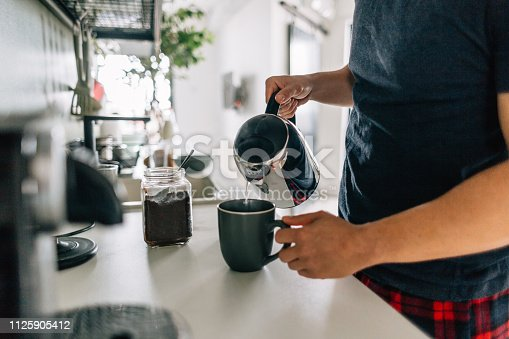 Young man preparing first cup of coffee in the morning in the kitchen of his apartment