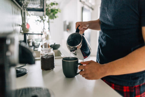 Preparing first cup of coffee in the morning Young man preparing first cup of coffee in the morning in the kitchen of his apartment routine stock pictures, royalty-free photos & images
