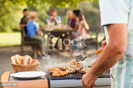 Rosting meat on barbecue for a family picnic in the back. Sun through the trees. Family at the table.