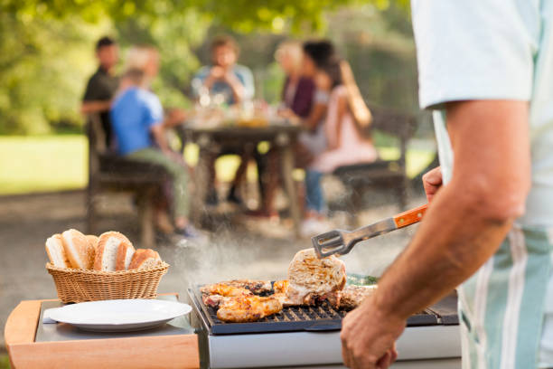 preparing food at picnic - barbecue grill stock photos and pictures