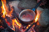 Preparing Food in Cooking Pot on Campfire.