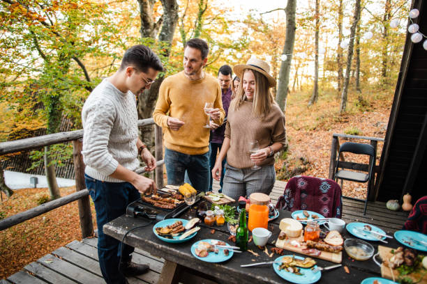 Preparing food outdoors together stock photo