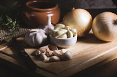 Garlic and onion, near a knife, upon a rustic wooden table, near a cooking pan and some green spices.