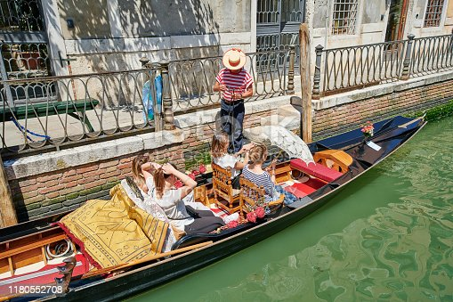 Venice, Italy - June 02, 2019: a gondolier prepares for a gondola tour with four female customers on board.