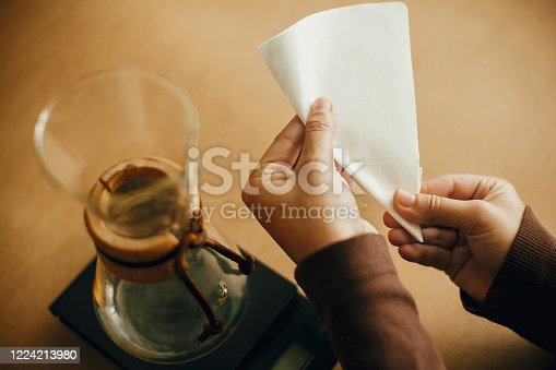 Preparing for alternative coffee brewing v60. Fold coffee filter. Hands folding paper filter for pour over and glass kettle on scale on brown background.