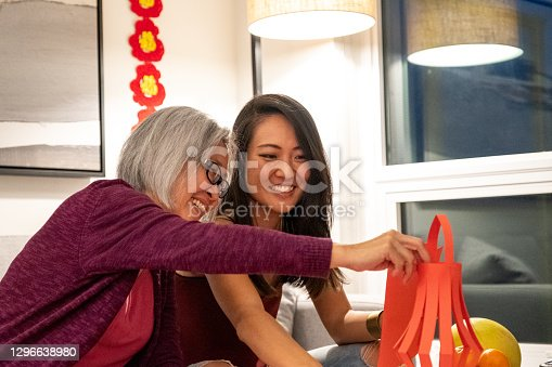 Mother and adult daughter making lanterns for Chinese New Years. Traditional Chinese New Years at home. Modern Chinese culture.