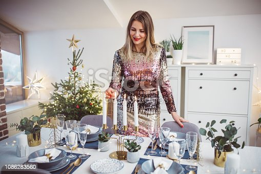 Woman lay the table for family Christmas meal. She arranging everything to be perfect for Christmas. Well dressed.